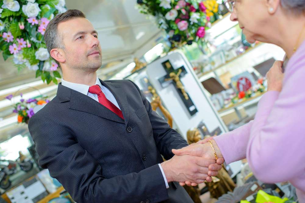 Funeral director shaking hands with elderly woman